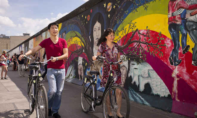 Ciclisti davanti alla East Side Gallery